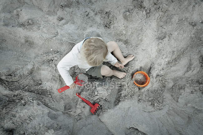 Overhead view of a boy sitting in sand pit with plastic shovel, bucket and rake — Stock Photo