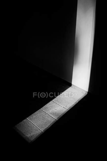 Elevated view of light spot on wall and floor of dark room — Stock Photo