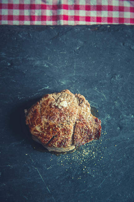 Spiced meat piece on black surface — Stock Photo