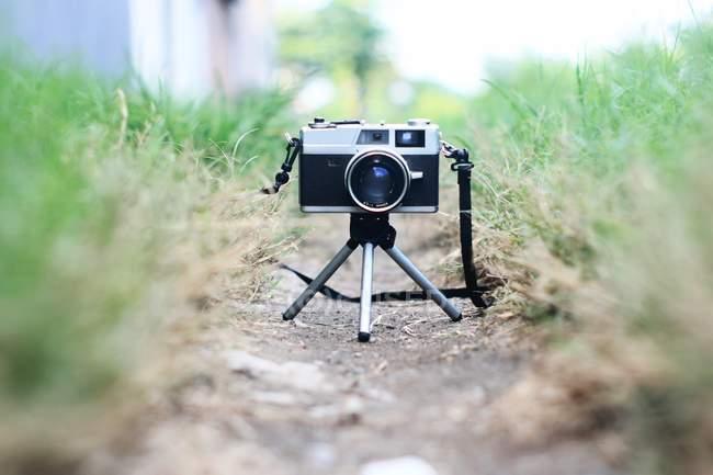 Macchina fotografica della pellicola dell'annata il treppiede su un terreno — Foto stock