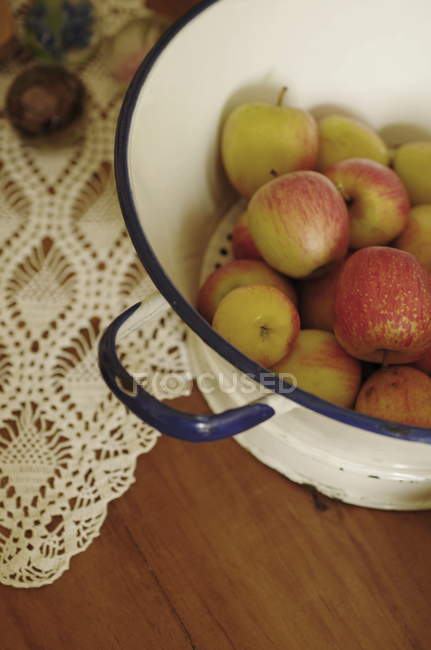 Fresh apples heap in strainer — Stock Photo