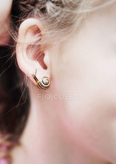 Close up of woman ear with Snail earring — Stock Photo