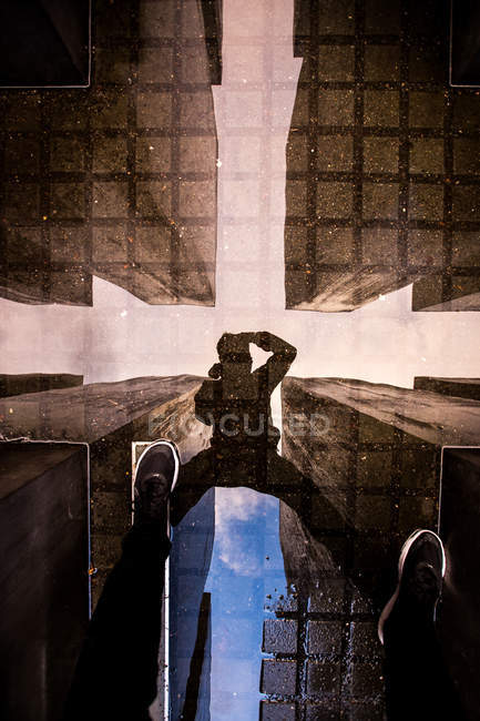Puddle with reflection of man against buildings taking photo on water surface — Stock Photo