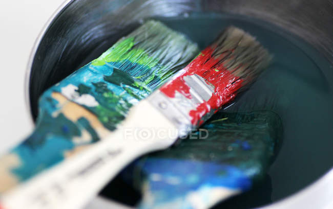 Dirty used paint brushes in bowl with water — Stock Photo