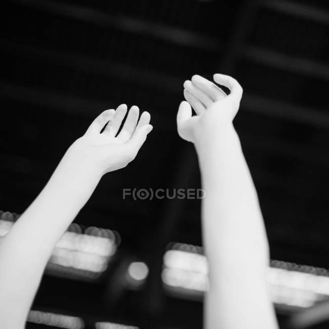 Cropped view of raised up female hands — Stock Photo