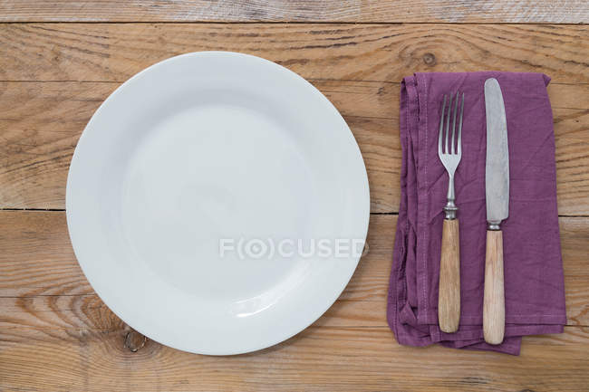 Top view of white plate with cutlery on table — Stock Photo
