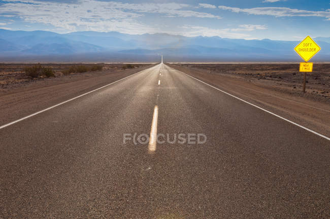 Asphalte de la route dans le désert et le panneau de signalisation jaune — Photo de stock