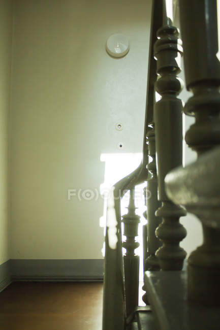 Daytime view of old wooden banister on staircase with light beam on white wall — Stock Photo