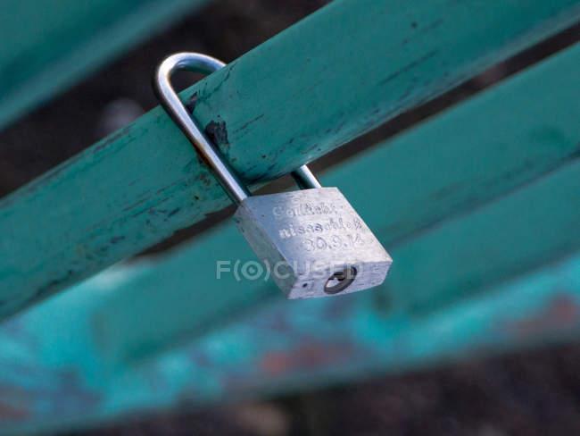 Metallic  padlock hanging on green steel railing — Stock Photo