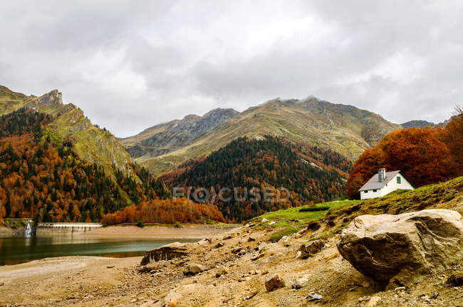 Autumn season in mountains with house and pond — Stock Photo