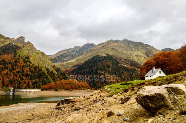Осенний сезон в горах с домом и пруд — стоковое фото
