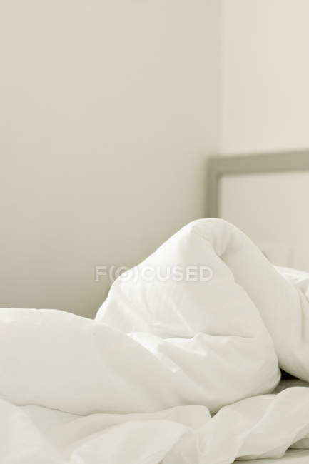 Comfortable light bedroom interior and crumpled white duvet on bed — Stock Photo