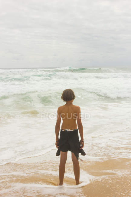 Boy at seashore in wetsuit — Stock Photo