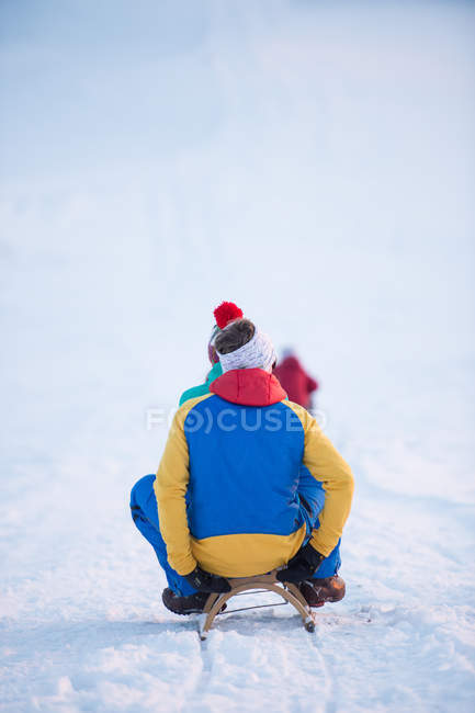 Rear view of kid sliding on slides at winter — Stock Photo