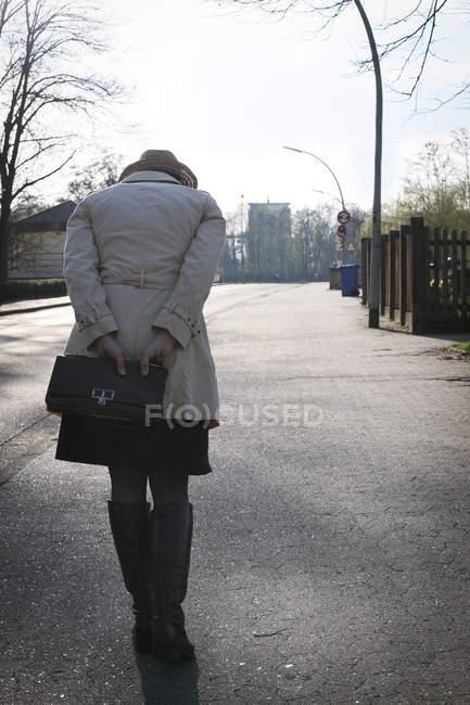 Rear view of woman in coat walking on street — Stock Photo