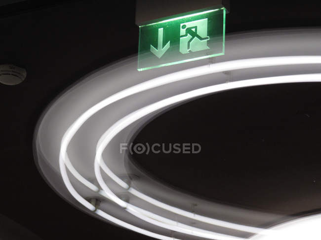 Green exit sign glowing in dusk, light trail on background — Stock Photo