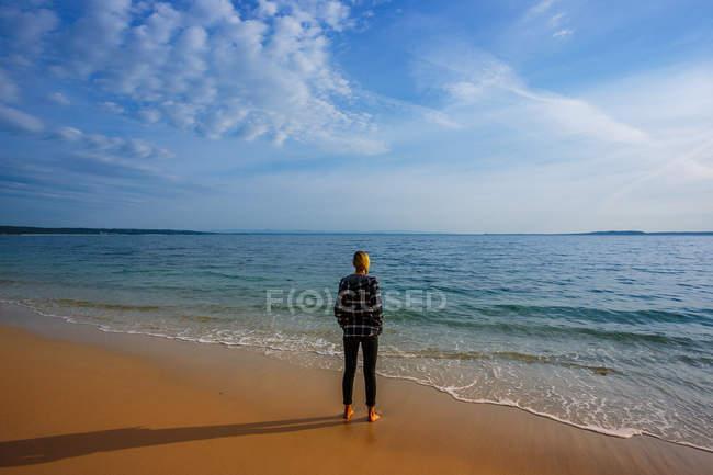 Vue arrière de la femme sur le bord de mer en soirée sunslight — Photo de stock