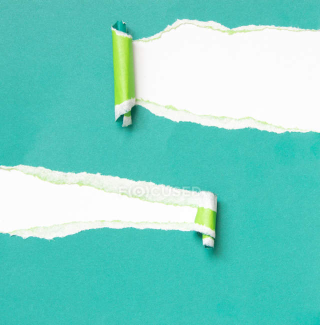 Torn papers on turquoise wall — Stock Photo