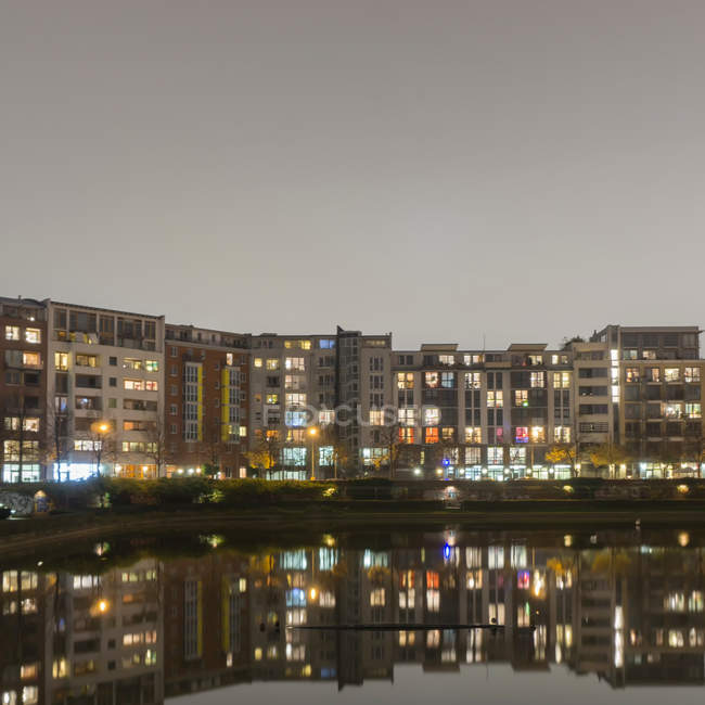 Residential houses area by the lake illuminated at night — Stock Photo