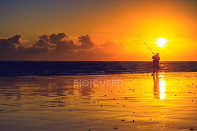 Pescador por do sol brilhante na beira-mar — Fotografia de Stock