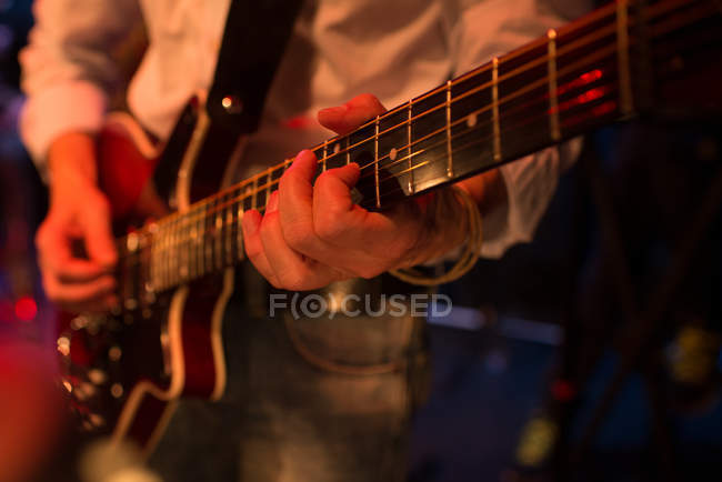 Partial view of guitarist playing guitar on stage — Stock Photo