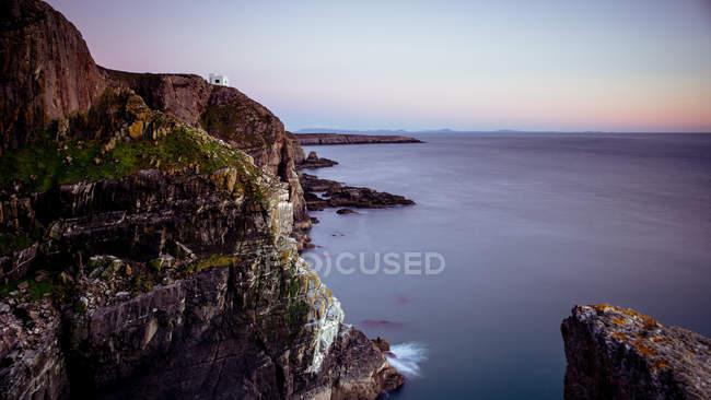 Скелястому узбережжі у заході сонця світлі — стокове фото