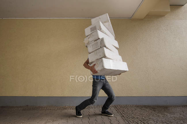 Man carrying many white heavy boxes, logistics — Stock Photo