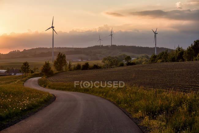 Fernsicht auf leere Straße, Windmühlen und Felder auf Hügeln, Sauerland — Stockfoto