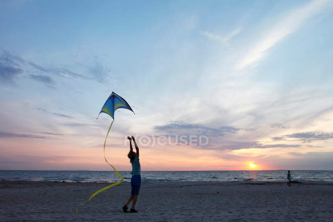 Seaside and girl playing with kite — Stock Photo