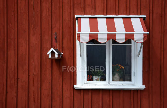 Exterior shot of red wooden house with window — Stock Photo