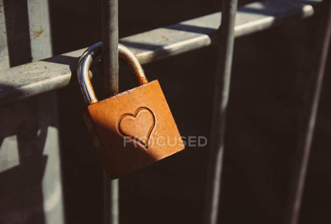 Padlock with heart sign on iron fence door — Stock Photo