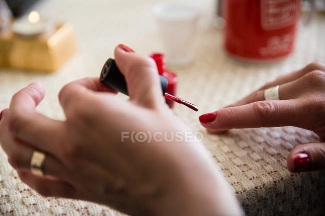 Cropped view of female hands painting nails with red nail polish — Stock Photo