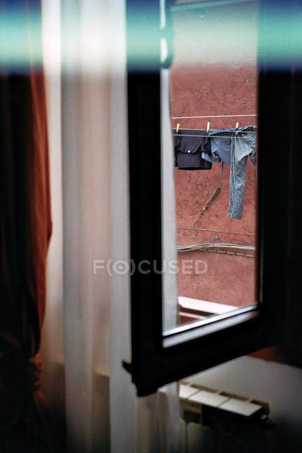 Clothesline with drying clothing view from open window with curtain — Stock Photo