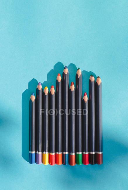 Dibujo multicolor crayolas lápices aislados sobre fondo azul - foto de stock