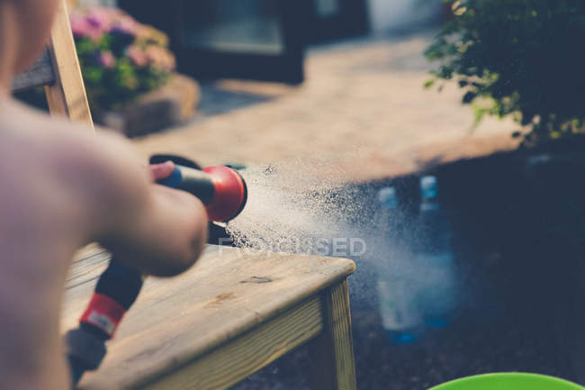 Cropped image of playful kid with watering hose in garden — Stock Photo
