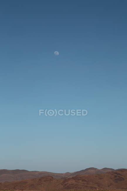 Desert landscape hills and moon in blue sky — Stock Photo