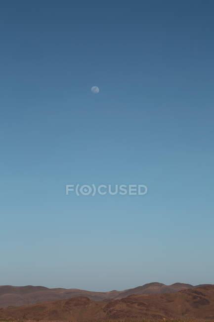 Paisaje colinas del desierto y la luna en cielo azul - foto de stock