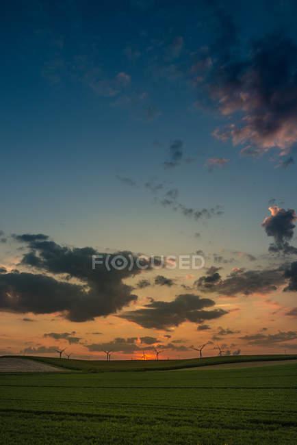 Sonnenuntergang Skyline mit landwirtschaftlichen Bereich und Windmühlen — Stockfoto