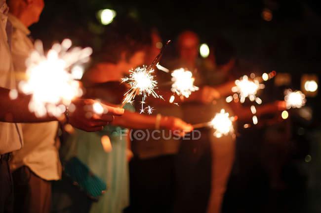 Юные друзья празднуют с Спарклер, тёмный фон — стоковое фото