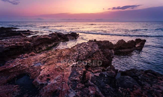 Скелястий берег подання на заході сонця — стокове фото