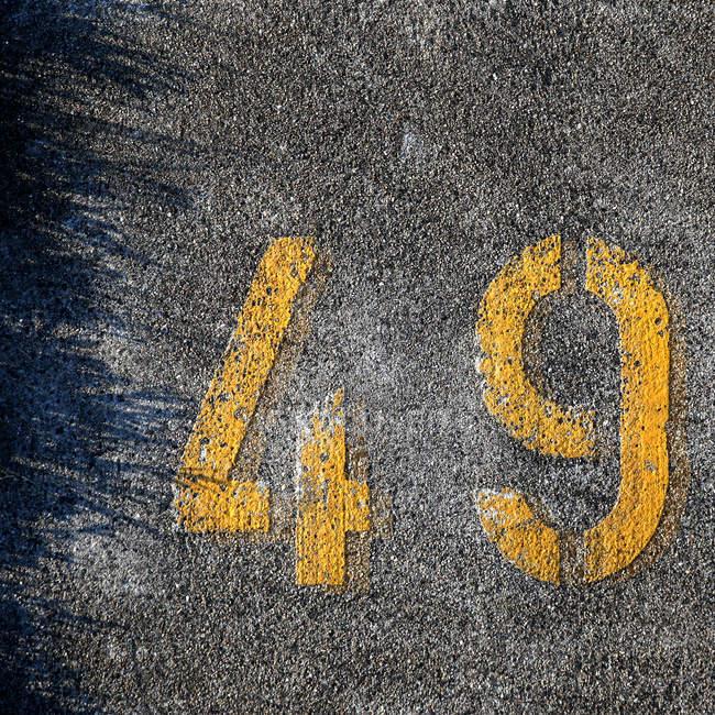 Обрезанное ввиду числа на асфальте — стоковое фото