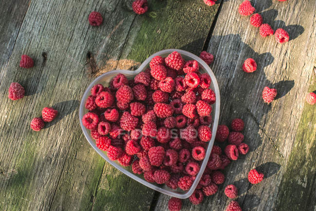 Raspberries in heart shaped bowl — Stock Photo