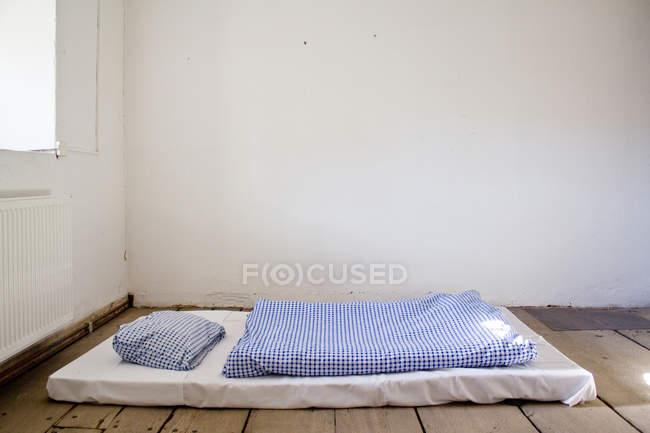 Poor interior, room with bed mattress on wooden floor — Stock Photo