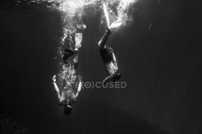 Young men diving in sea wearing masks and flippers — Stock Photo