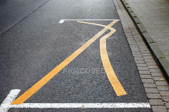 Strada asfaltata con linee curva gialla — Foto stock