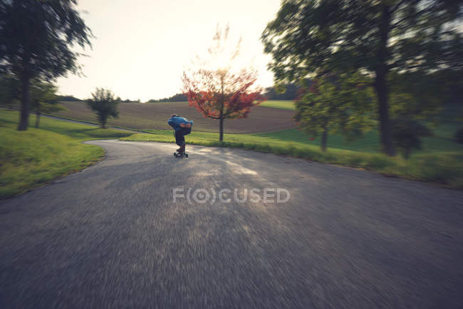 Back view of man riding fast long board on road — Stock Photo