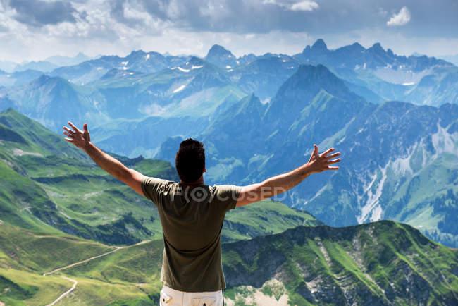 Glücklich Reisenden Mann in Bergen und ausgestreckten Händen halten — Stockfoto