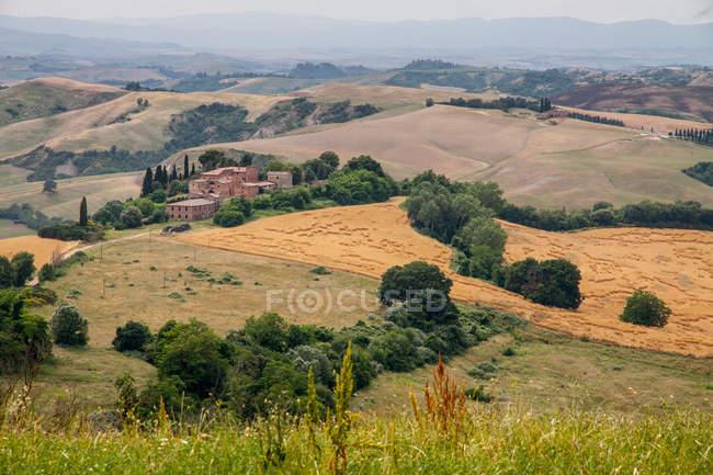 Сільській місцевості пагорби поля з будинків — стокове фото