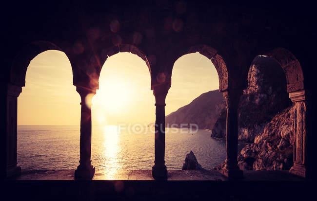 Bord de mer passant sous une arche antique — Photo de stock