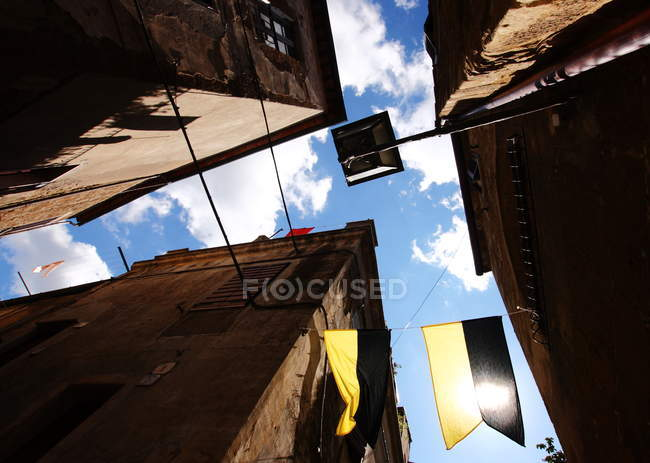 Bottom view of residential houses with flags on street of old Tuscany town, Italy — Stock Photo
